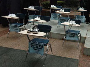 Enough desks to fill a classroom sat empty in a downtown plaza Tuesday, each bearing a pair of sneakers and representing one of 20 Chicago Public Schools students killed by gunfire this school year. (AP)