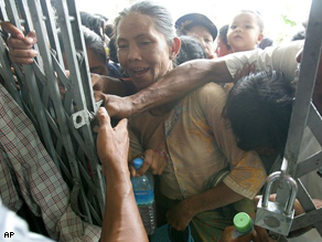 Victims of Cyclone Nargis rush to get first in line to receive donated goods from a local donor at a monastery outside the capital of Yangon, Myanmar on Monday May 19, 2008.