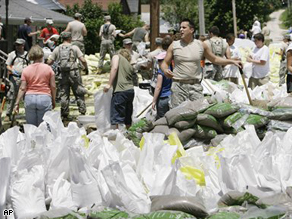 Residents, volunteers and National Guard troops work to build a sand bag levee around the town of in Hamburg, Ill. Friday, June 20.