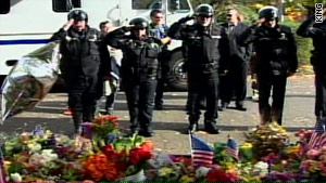 Seattle police salute during a memorial for their slain comrade, Officer Timothy Brenton.