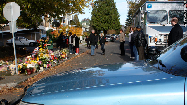 Flowers are placed on the street earlier this week where Officer Timothy Brenton was shot and killed.