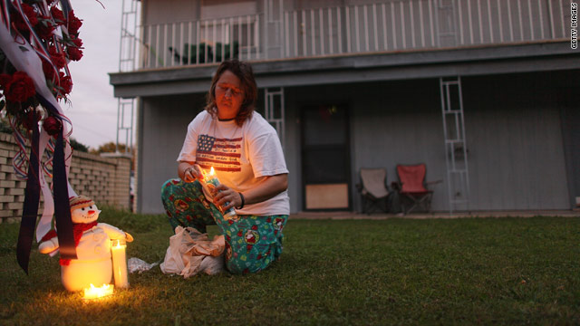 A neighbor of Maj. Nidal Malik Hasan, who did not want to be named, lights candles in the courtyard of their apartment complex.