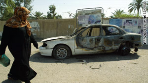 An Iraqi woman passes a burnt car on the site where Blackwater guards opened fire in western Baghdad.