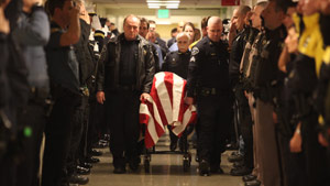 "Police officers escort the body of their slain colleague, Deputy  Walter ""Kent"" Mundell Jr."