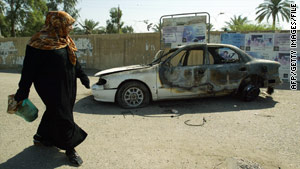 A woman passes a burnt-out car in the aftermath of the 2007 shootout in Baghdad, Iraq.