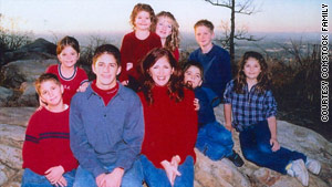 Cindy Comstock is surrounded by her eight children.