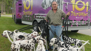 Trainer Joel Slaven shows off some of the Dalmatians outside the musical show's traveling bus and trailer.