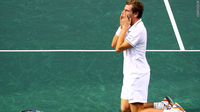 Frenchman Julien Benneteau sinks to his knees after a famous victory over world No.1 Roger Federer.