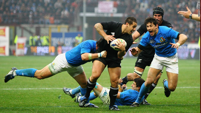 Luke McAlister of the All Blacks is tackled in the San Siro clash.