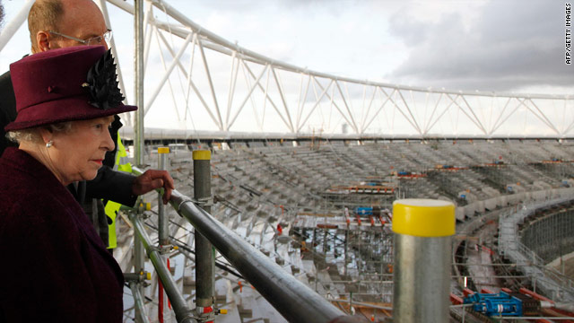 Queen Elizabeth is shown around the site of the London Olympic stadium.
