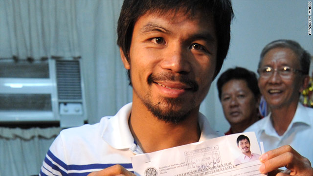 Manny Pacquiao holds his registration certificate after filing in the town of Alabel in Saragani province.