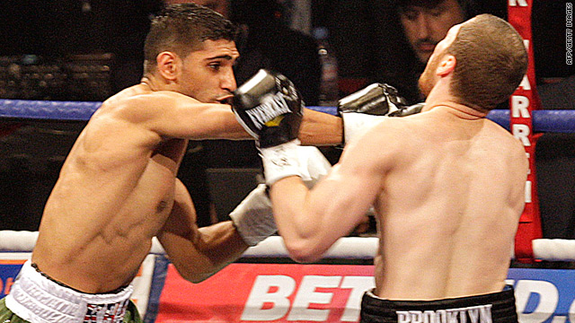 Amir Khan, left, pummeled challenger Dmitriy Salita into submission to defend his world title.