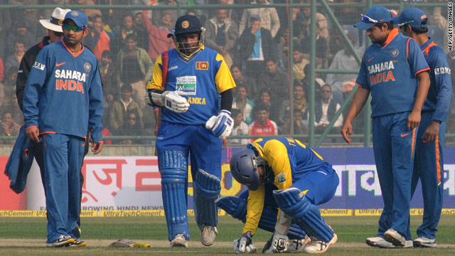 Batsman Tillekaratne Dilshan is watched by Sri Lanka teammate Sanath Jayasuriya and Indian fielders after being hit.