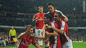 Merida is surrounded by teammates after his superb opener for Arsenal.