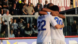 Diego Milito is congratulated by team-mates after scoring Inter's opening goal in their win at Livorno.