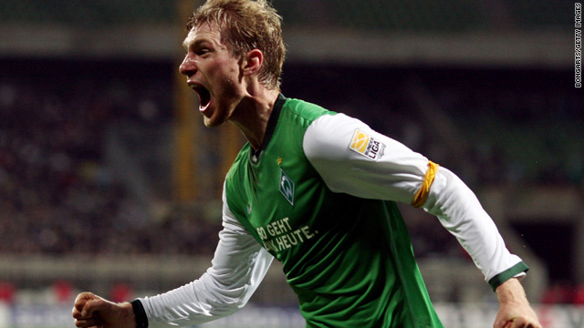 Per Mertesacker celebrates after scoring the late goal that put Werder Bremen on top on goal difference.