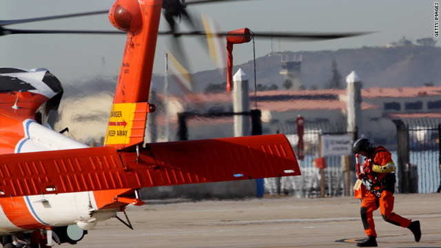 A Coast Guard search team member approaches a helicopter Friday in San Diego, California.