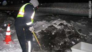Crews collect contaminated snow below the ruptured pipeline.