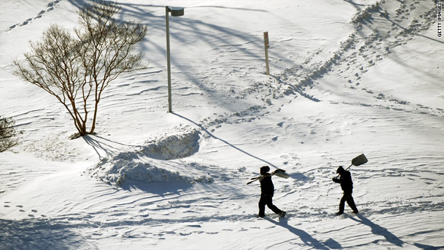 Two men with snow shovels make their way through a mantle of white in Silver Spring, Maryland, on Sunday.
