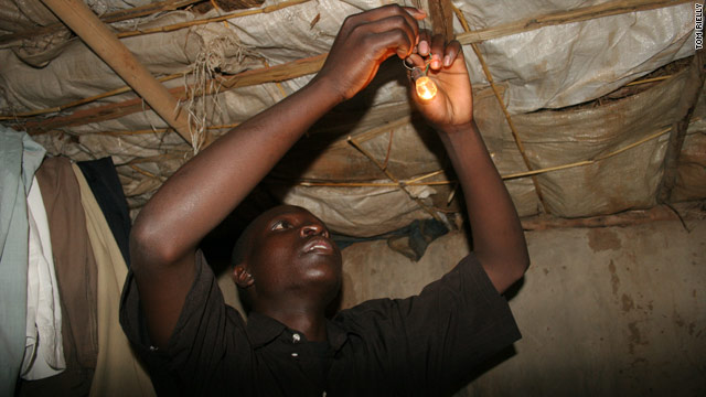 William Kamkwamba fits a lightbulb to a house in his village in Malawi.