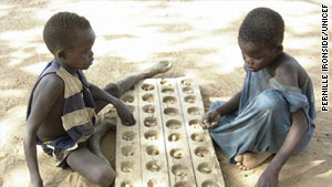 Young boys play a local boardgame in Malualkon, southern Sudan.