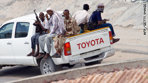 Somalian soldiers pass an African Union Mission in Somalia base in Mogadishu, on November 24, 2009.
