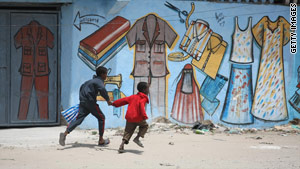 Children run past the frontline amid clashes between Somali soldiers and insurgents in August 2009.
