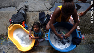 A resident of Caracas washes clothes in the street; the government has imposed water rations due to drought.