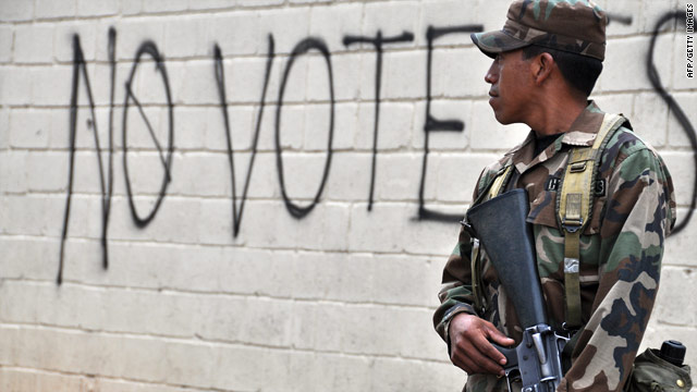 A Honduran soldier stands guard Friday in Tegucigalpa near graffiti urging a boycott of this weekend's election.