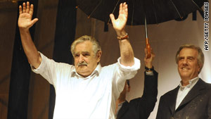 Jose Mujica waves to supporters Sunday as outgoing Uruguyan President Tabare Vazquez, right, looks on.