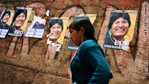 A woman walks past posters urging the re-election of Bolivian President Evo Morales on the eve of voting.