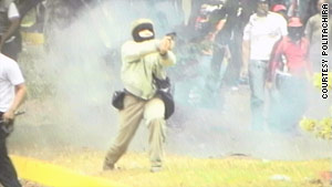 A state police photo appears to show a masked man firing a handgun Tuesday at unarmed demonstrators.