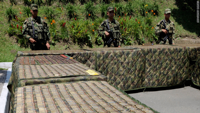 Colombian soldiers stand next to tables with thousands of seized cartridges put on display on May 6, 2009, in Medellin, Antioquia Department, which were seized from FARC leftist guerrillas.