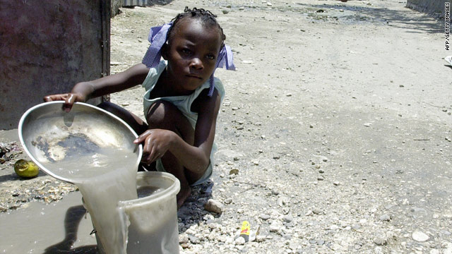 A Haitian child works on 11 May, 2007, in front of her house in Cite Soleil, the biggest slum of the capital Port-au-Prince.