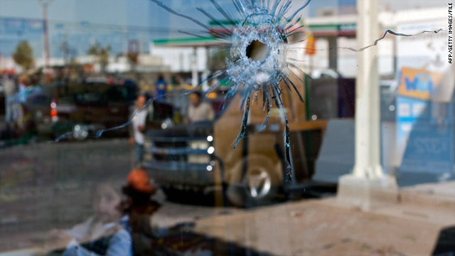 A young girl is visible through bullet-pierced glass near the spot where two Ciudad Juarez policemen were killed in November.