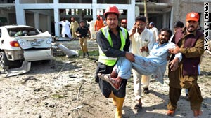 Rescuers carry a man hurt in Friday's blast in Peshawar.