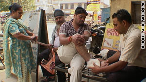 Chaman Lal treats this man, who has injured his ankle. Lal says his potion of 18 herbs is a cure-all.