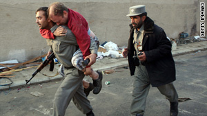 An injured man is carried on the back of a policeman following the attack in Kabul on Wednesday.
