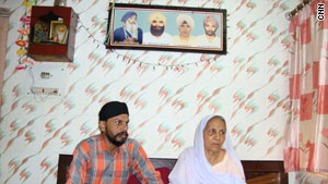Gurdeep Kaur, right, and her son sit on a bed below a picture of the slain family members.
