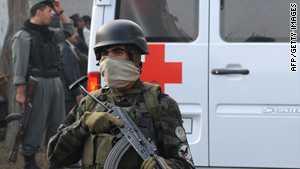 An Afghan police officer guards an ambulance carrying victims of the attack that killed five U.N. personnel.