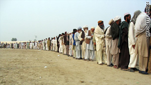 Displaced tribesmen, fleeing from military operations in South Waziristan queue for aid on November 2, 2009.