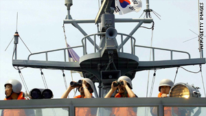 South Korean Navy sailors signal a North Korean warship on the western maritime border on 14 June 2004.