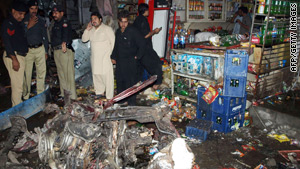 Police stand next to wreckage of vehicles destroyed in Tuesday's suicide bombing in Charsadda.