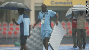 Groundsmen rush to cover the pitch in Mumbai as rain falls ahead of a cricket match between India and Australia.