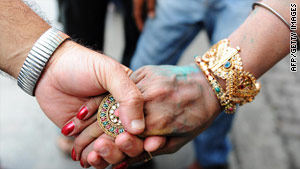 A member of the gay, lesbian and transgender community holds hands with a eunuch after a court ruling on gay sex.
