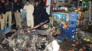 Pakistani police stand beside the wreckage from a suicide car bomb in Peshawar on Tuesday.