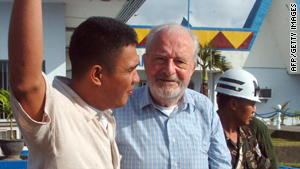Released Irish priest Michael Sinnott, center, is escorted at a military airbase in Zamboanga City on Thursday.