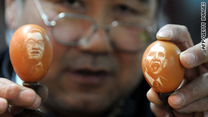 Chinese artist Kang Yongguo shows off egg paintings Sunday of President Obama and President Hu Jintao.