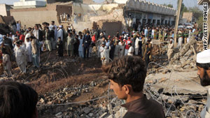 Local residents gather at the site of a suicide car bomb blast on the outskirts of Peshawar.