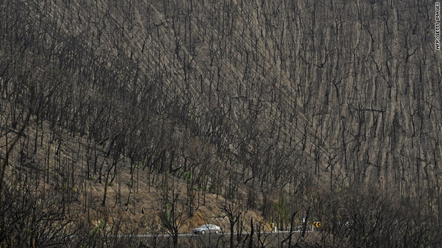 A car drives through a landscape devastated by bushfires in February near Kinglake, 60 kilometers north of Melbourne.
